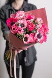 χαριτωμένα λουλούδια όμορφη ανθοδέσμη των ρόδινων anemones στο χέρι γυναικών η εργασία του ανθοκόμου σε ένα ανθοπωλείο οικογένεια Στοκ Εικόνες