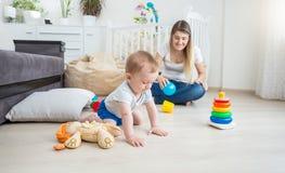 Χαριτωμένα 10 μηνών παιχνιδιού μωρών στο πάτωμα με τα ζωηρόχρωμα παιχνίδια Στοκ Εικόνες