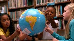 Χαριτωμένα μικρά κορίτσια που εξετάζουν τη σφαίρα στη βιβλιοθήκη απόθεμα βίντεο