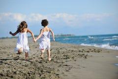 Χαριτωμένα μικρά κορίτσια που τρέχουν στην παραλία στοκ φωτογραφίες