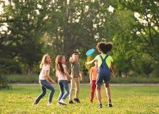Χαριτωμένα μικρά παιδιά που παίζουν με το frisbee υπαίθρια στοκ εικόνες με δικαίωμα ελεύθερης χρήσης