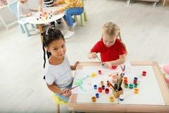 Χαριτωμένα μικρά παιδιά που χρωματίζουν στο μάθημα στοκ εικόνα με δικαίωμα ελεύθερης χρήσης
