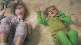 Χαριτωμένα μικρά παιδιά στις πυτζάμες που κυλούν στο πάτωμα με το χνουδωτό τάπητα Ο αδελφός και η αδελφή έχουν μια διασκέδαση Ευτ απόθεμα βίντεο