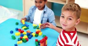 Χαριτωμένα μικρά παιδιά που παίζουν με τις δομικές μονάδες στον πίνακα απόθεμα βίντεο