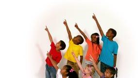 Χαριτωμένα μικρά παιδιά όλα που δείχνουν επάνω στο άσπρο υπόβαθρο απόθεμα βίντεο