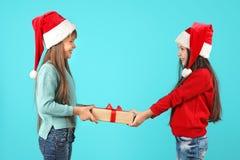 Χαριτωμένα παιδιά στα καπέλα Santa με το δώρο Χριστουγέννων στο υπόβαθρο χρώματος Στοκ φωτογραφία με δικαίωμα ελεύθερης χρήσης