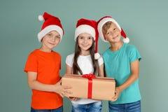 Χαριτωμένα παιδιά στα καπέλα Santa με το κιβώτιο δώρων Χριστουγέννων στο υπόβαθρο χρώματος Στοκ Φωτογραφίες
