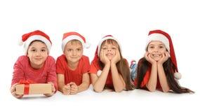 Χαριτωμένα παιδιά στα καπέλα Santa στο άσπρο υπόβαθρο γιορτάστε τη φθορά santa μητέρων καπέλων κορών Χριστουγέννων εορτασμού Στοκ φωτογραφία με δικαίωμα ελεύθερης χρήσης