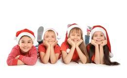 Χαριτωμένα παιδιά στα καπέλα Santa στο άσπρο υπόβαθρο γιορτάστε τη φθορά santa μητέρων καπέλων κορών Χριστουγέννων εορτασμού Στοκ Εικόνες