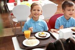 Χαριτωμένα παιδιά στον πίνακα με τα υγιή τρόφιμα στο σχολείο στοκ εικόνες