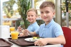 Χαριτωμένα παιδιά στον πίνακα με τα υγιή τρόφιμα στο σχολείο στοκ φωτογραφίες