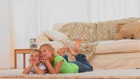 Χαριτωμένα παιδιά που προσέχουν τη TV απόθεμα βίντεο