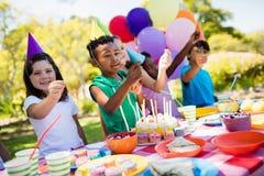 Χαριτωμένα παιδιά που χαμογελούν και που έχουν τη διασκέδαση κατά τη διάρκεια μιας γιορτής γενεθλίων στοκ εικόνες