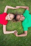 Χαριτωμένα παιδιά που χαμογελούν στη κάμερα έξω στη χλόη Στοκ εικόνες με δικαίωμα ελεύθερης χρήσης