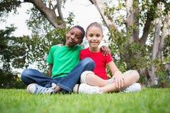 Χαριτωμένα παιδιά που χαμογελούν στη κάμερα έξω στη χλόη Στοκ εικόνα με δικαίωμα ελεύθερης χρήσης