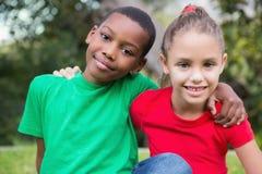 Χαριτωμένα παιδιά που χαμογελούν στη κάμερα έξω στη χλόη Στοκ Φωτογραφία