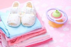 Χαριτωμένα παπούτσια μωρών για τα παιδιά στο σωρό των ενδυμάτων μωρών Στοκ φωτογραφία με δικαίωμα ελεύθερης χρήσης