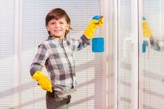 Χαριτωμένα παράθυρα πλύσης αγοριών στα κίτρινα λαστιχένια γάντια Στοκ Φωτογραφίες