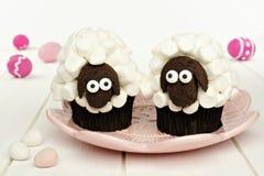 Χαριτωμένα πρόβατα άνοιξη cupcakes στο ρόδινο πιάτο με τα αυγά Πάσχας στοκ εικόνες