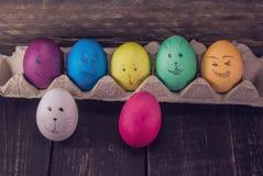 Χαριτωμένα πρόσωπα αυγών Πάσχας στο ξύλινο υπόβαθρο Αστεία διακόσμηση Στοκ εικόνα με δικαίωμα ελεύθερης χρήσης