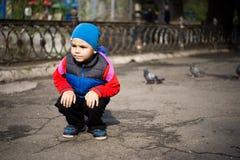Χαριτωμένα ταΐζοντας πουλιά μικρών παιδιών στο πάρκο πόλεων Καιρός φθινοπώρου ή άνοιξης Στοκ Εικόνες