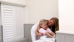 Χαριτωμένα χέρια πλύσης μικρών κοριτσιών με τη μητέρα της απόθεμα βίντεο