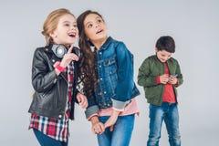 Χαριτωμένα χαμογελώντας κορίτσια που ανατρέχουν ενώ αγόρι που χρησιμοποιεί το smartphone Στοκ Φωτογραφία