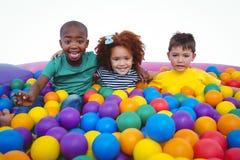 Χαριτωμένα χαμογελώντας παιδιά στη λίμνη σφαιρών σφουγγαριών Στοκ Εικόνα
