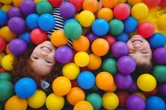 Χαριτωμένα χαμογελώντας παιδιά στη λίμνη σφαιρών σφουγγαριών Στοκ Φωτογραφία