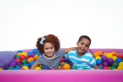 Χαριτωμένα χαμογελώντας παιδιά στη λίμνη σφαιρών σφουγγαριών Στοκ εικόνες με δικαίωμα ελεύθερης χρήσης