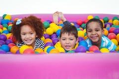 Χαριτωμένα χαμογελώντας παιδιά στη λίμνη σφαιρών σφουγγαριών Στοκ Εικόνες