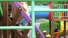 Χαριτωμένα 5χρονα παιχνίδια κοριτσιών στην παιδική χαρά και αναβάσεις επάνω στα σκαλοπάτια απόθεμα βίντεο
