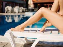 Χαριτωμένα, όμορφα και προκλητικά νέα πόδια γυναικών ` s σε ένα υπόβαθρο λιμνών Στοκ Φωτογραφία