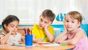 Χαριτωμένα preschoolers που σύρουν με τα ζωηρόχρωμα μολύβια Στοκ Εικόνες