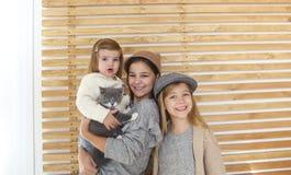 Χαριτωμένες αδελφές μικρών κοριτσιών μόδας με ένα βρετανικό γατάκι στα όπλα στοκ εικόνα