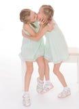 Χαριτωμένες αδελφές που έχουν τη συνεδρίαση διασκέδασης σε μια καρέκλα. Στοκ εικόνα με δικαίωμα ελεύθερης χρήσης