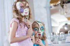 Χαριτωμένες αδελφές που θέτουν τα κρύβοντας πρόσωπα πίσω από τις μάσκες Στοκ Φωτογραφία