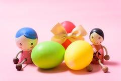Χαριτωμένες κούκλες και ζωηρόχρωμα αυγά Πάσχας στο ρόδινο υπόβαθρο Στοκ εικόνες με δικαίωμα ελεύθερης χρήσης