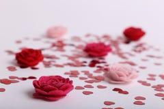 Χαριτωμένες κόκκινες διεσπαρμένες καρδιές τσεκιών με τα λουλούδια υφάσματος σε ένα άσπρο υπόβαθρο Στοκ εικόνα με δικαίωμα ελεύθερης χρήσης