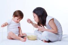 Χαριτωμένες μικρές εύθυμες αδελφές που τρώνε τα yummy ζυμαρικά στο άσπρο υπόβαθρο στούντιο Στοκ Φωτογραφία