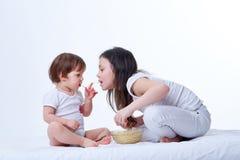 Χαριτωμένες μικρές εύθυμες αδελφές που τρώνε τα yummy ζυμαρικά στο άσπρο υπόβαθρο στούντιο Στοκ Εικόνες