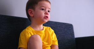 Χαριτωμένες νεολαίες λίγη τηλεόραση προσοχής παιδιών σε έναν καναπέ κ απόθεμα βίντεο