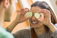 Χαριτωμένες φέτες αγγουριών εκμετάλλευσης brunette πέρα από τα μάτια Στοκ φωτογραφία με δικαίωμα ελεύθερης χρήσης