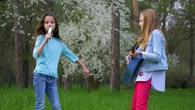 Χαριτωμένες φίλες εφήβων που παίζουν την κιθάρα του υπαίθρια τα μικρά κορίτσια τραγουδούν την τρίχα και το χορό χτενών τραγουδιών φιλμ μικρού μήκους