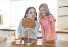 Χαριτωμένες χαμογελώντας μητέρα και κόρη που εφαρμόζουν την κρέμα προσώπου στοκ φωτογραφία