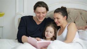 Χαριτωμένη λίγη κόρη διαβάζει μεγαλοφώνως ένα βιβλίο στη γλώσσα Foreing που βρίσκεται στο κρεβάτι, οι γονείς της γελούν σε μερικο φιλμ μικρού μήκους