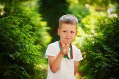Χαριτωμένη αγόρι, εκμετάλλευση και παρουσίαση αθλητικής ημέρας αγγελιών μεταλλίων Στοκ φωτογραφία με δικαίωμα ελεύθερης χρήσης