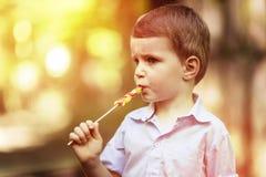 Χαριτωμένη απορρόφηση παιδιών σε ένα lollipop στοκ φωτογραφία