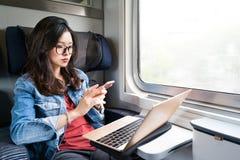 Χαριτωμένη ασιατική γυναίκα που χρησιμοποιούν το smartphone και το lap-top στο τραίνο, διάστημα αντιγράφων στο παράθυρο, επιχειρη Στοκ Εικόνες
