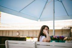 Χαριτωμένη ασιατική νέα γυναίκα στο θερινό καφέ υπαίθρια κορίτσι στην άσπρη μπλούζα, με μακρυμάλλη στο απλό ελαφρύ άνετο εσωτερικ Στοκ φωτογραφία με δικαίωμα ελεύθερης χρήσης
